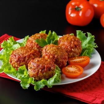 Boulettes de viande appétissantes à la sauce tomate sur un espace sombre. plat riche en protéines.