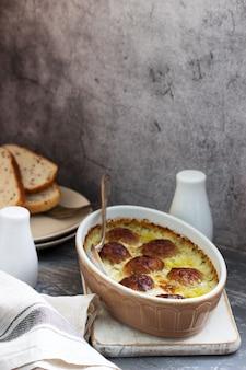 Boulettes de viande au four dans une sauce crémeuse et des tranches de pain avec du lin sur une surface en béton