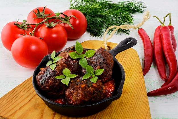 Boulettes de viande au piment rouge et à la tomate servies dans une poêle en fonte