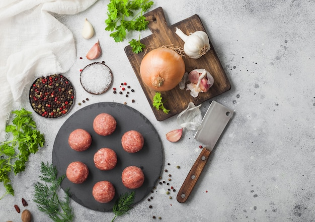 Boulettes de viande de boeuf frais sur planche de pierre avec du poivre, du sel et de l'ail sur une surface légère avec de l'aneth, du persil et de l'aneth et l'oignon. vue de dessus