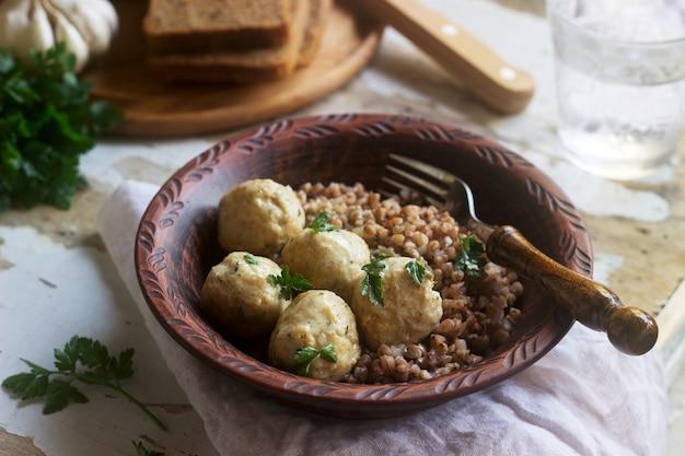 Boulettes de viande à la crème sure, accompagnées de porridge de sarrasin, de pain et d'ail. style rustique.
