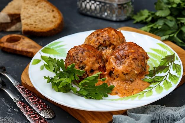 Boulettes de viande à la crème sure et sauce tomates dans une assiette blanche contre une planche de bois,