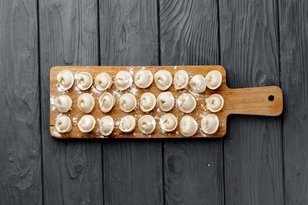Boulettes de viande crue sur planche de bois sur table