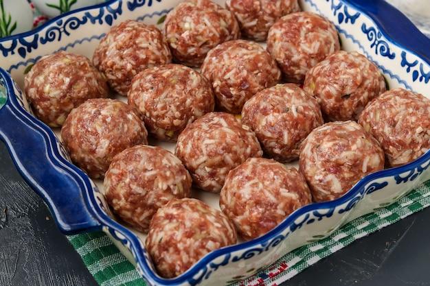 Boulettes de viande crues avec du riz cuisent sous forme de céramique, orientation horizontale