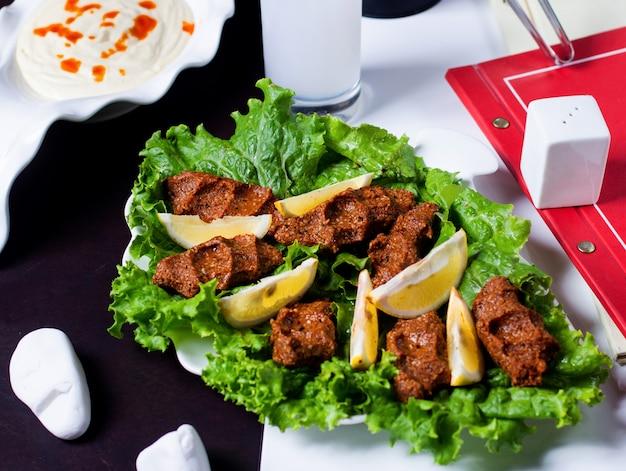 Boulettes de viande crues épicées turques cig kofte servies avec du citron et de la laitue