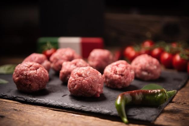 Boulettes de viande crues sur plaque de basalte foncé close up