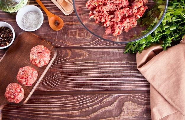Boulettes de viande crues sur le plateau en bois avec des ingrédients sur l'arrière-plan