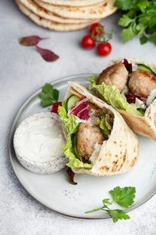 Boulettes de viande dans un pita avec salade de légumes et sauce au yogourt