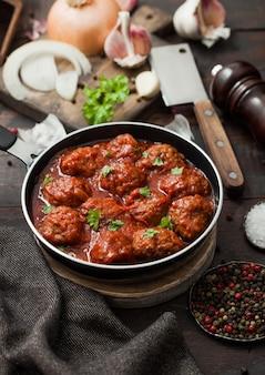 Boulettes de viande épicées traditionnelles à la sauce tomate avec du poivre, de l'ail et du persil avec l'oignon et le couperet sur une surface noire.