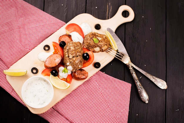 Boulettes de viande grecques maison juteuses servies avec salade de légumes, sauce au citron vert et yaourt.