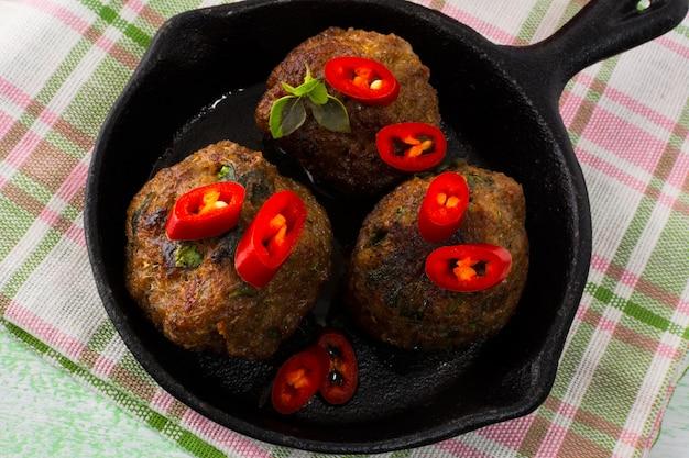 Boulettes de viande grillées avec des tranches de piment rouge