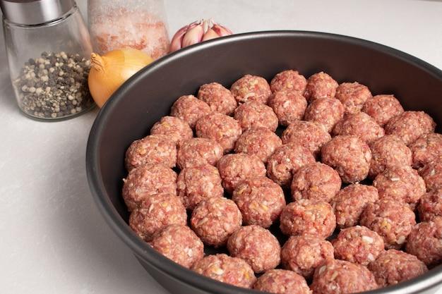 Boulettes de viande hachée crue prête au concept de cuisine préparatoire sur fond clair