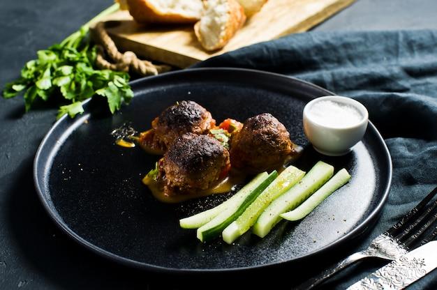 Boulettes de viande italiennes à la sauce tomate sur une assiette noire, concombres, sel, pain.