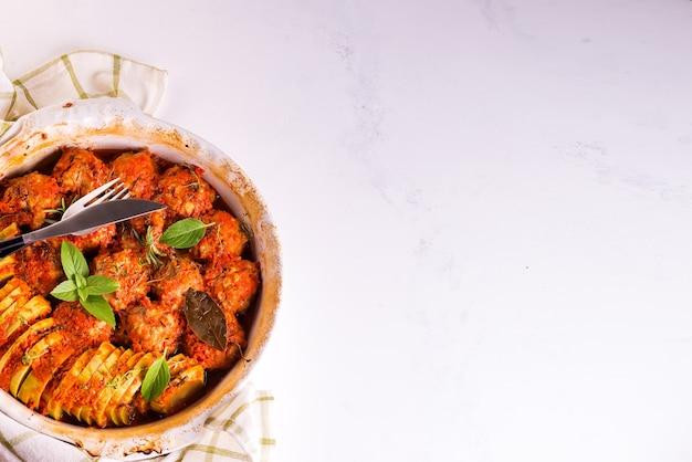 Boulettes de viande maison avec sauce tomate dans un plat blanc cuit au four avec des herbes sur une surface en marbre blanc