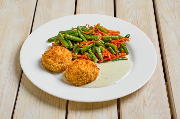 Boulettes de viande panées servies avec haricots verts et carotte épicée