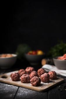 Boulettes de viande sur planche de bois et ingrédients