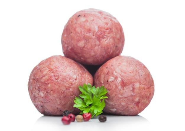 Boulettes de viande de porc au boeuf avec du poivre et du persil sur blanc.