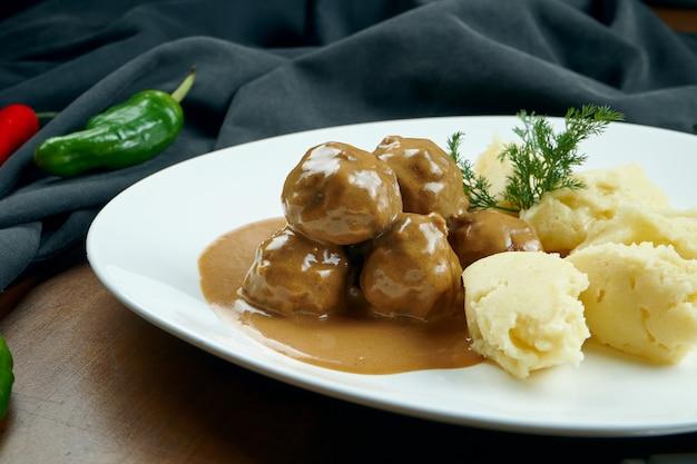 Boulettes de viande de poulet appétissantes en sauce avec un plat d'accompagnement de purée de pommes de terre dans une assiette blanche sur une table en bois dans une composition avec des ingrédients