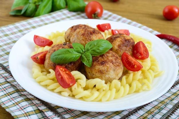 Boulettes de viande de poulet, pâtes fusilli, tomates, basilic sur une plaque blanche