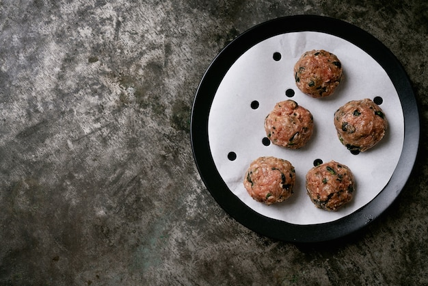 Boulettes de viande prêtes à cuire dans une assiette noire sur du papier sulfurisé. mise à plat. vue de dessus