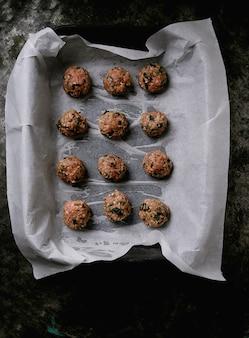 Boulettes de viande prêtes à cuire dans une plaque en céramique noire sur du papier sulfurisé, à plat. vue de dessus