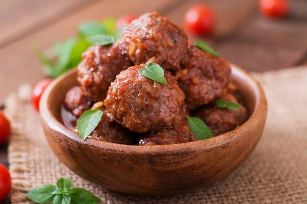 Boulettes de viande à la sauce tomate aigre-douce et basilic dans un bol en bois