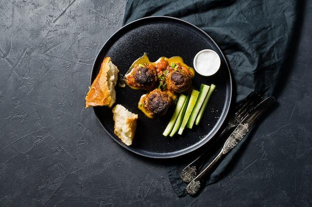 Boulettes de viande à la sauce tomate sur une assiette noire, concombres, sel, pain.