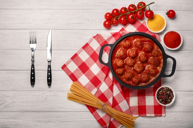 Boulettes de viande à la sauce tomate avec des épices dans une poêle à frire sur une planche de bois blanche