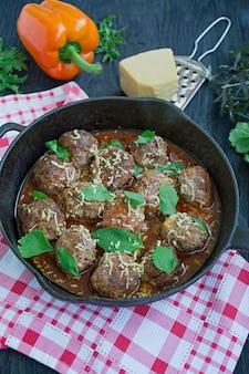 Boulettes de viande à la sauce tomate avec des légumes verts.