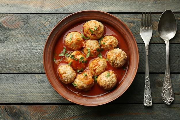 Boulettes de viande à la sauce tomate, sur table en bois