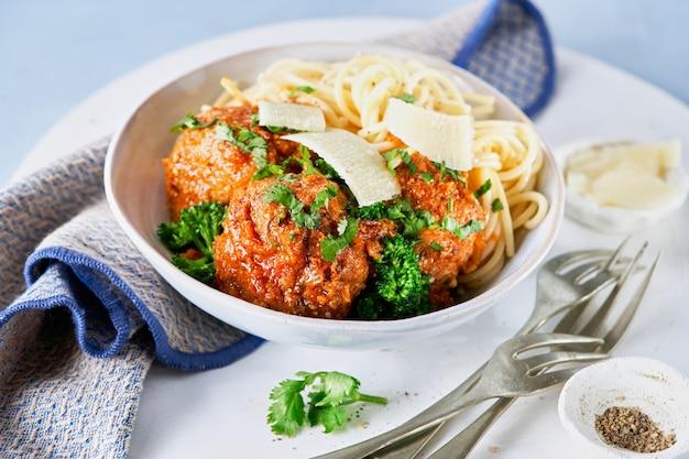 Boulettes de viande avec spaghetti, sauce tomate, crumbles de parmesan, broccolini, fleurettes de brocoli, dîner sain végétalien, déjeuner.