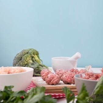 Boulettes de viande vue de face sur planche de bois avec des ingrédients
