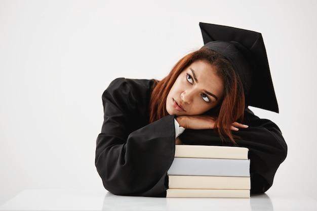 Bouleversé diplômé africain couché sur des livres pensant assis. copiez l'espace.