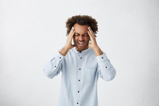 Bouleversé étudiant masculin serrant la tête avec les mains