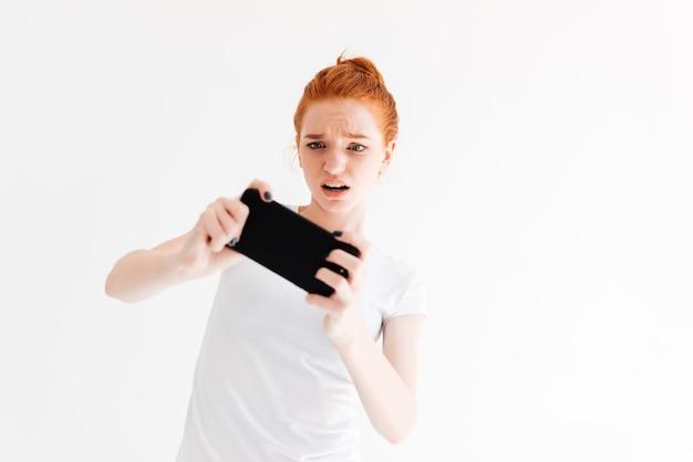 Bouleversé la femme au gingembre en t-shirt jouant sur son smartphone
