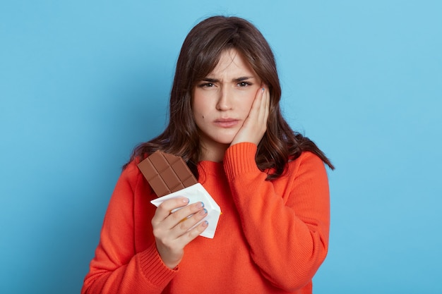 Bouleversé femme caucasienne tenant une barre de chocolat dans les mains, se sent mal aux dents après avoir mordu des bonbons, couvrant la joue avec la paume, portant un pull décontracté, isolé sur un mur bleu. soins de santé.