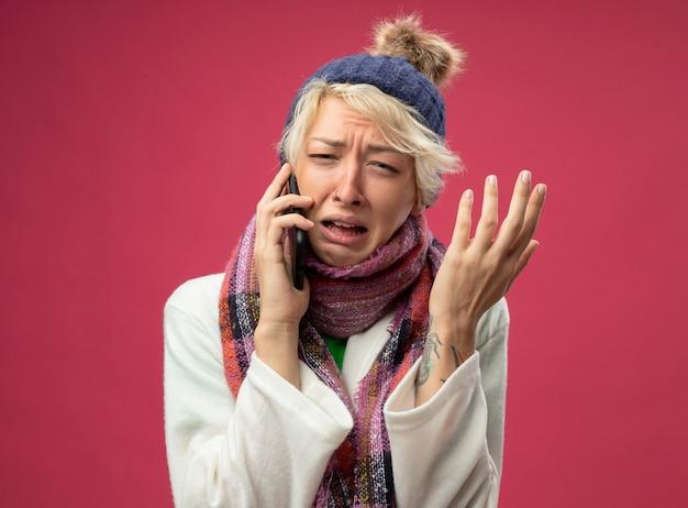 Bouleversé femme malsaine malade avec les cheveux courts dans une écharpe chaude et un chapeau se sentant mal pleurer tout en parlant au téléphone mobile avec le bras levé debout sur fond rose