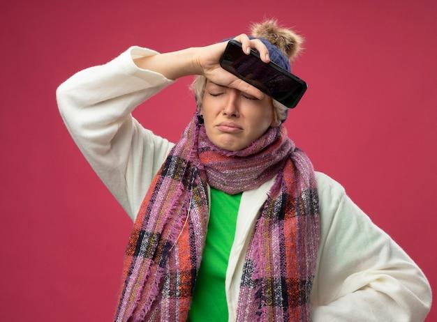 Bouleversé femme malsaine malade avec les cheveux courts dans une écharpe chaude et un chapeau se sentant mal tenant la main sur son front avec smartphone debout sur le mur rose