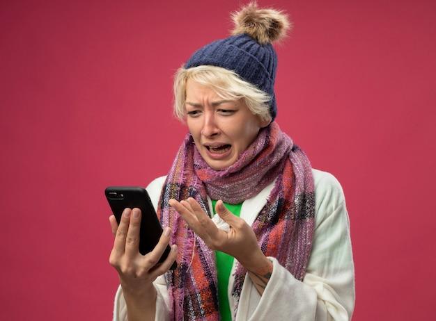 Bouleversé femme malsaine malade avec les cheveux courts dans une écharpe chaude et un chapeau se sentant malade, stressé et frustré lookign à son écran de smartphone debout sur fond rose