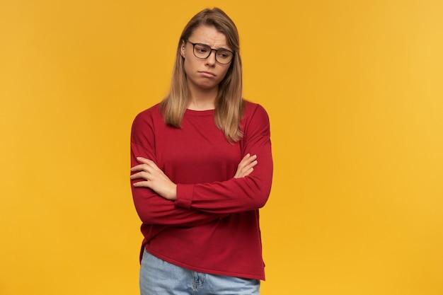 Bouleversé fille blonde portant des lunettes gonflées joues regardant vers le bas vers le coin droit debout avec les bras croisés isolés