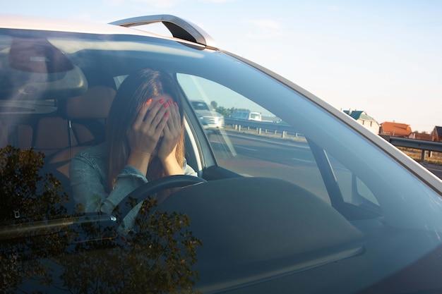 Bouleversé, fille fatiguée conduisant une voiture.