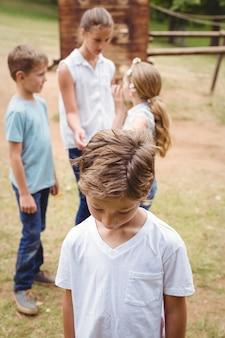Bouleversé garçon avec des amis commérages en arrière-plan