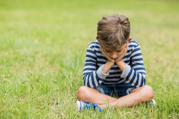 Bouleversé garçon assis sur l'herbe