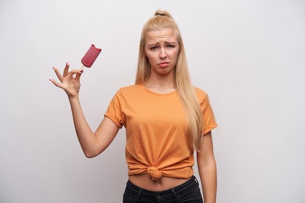 Bouleversé jeune femme blonde aux cheveux longs dans des vêtements décontractés, fronçant les sourcils et regardant la caméra avec la moue tout en tenant la glace sur le bâton, posant sur fond blanc