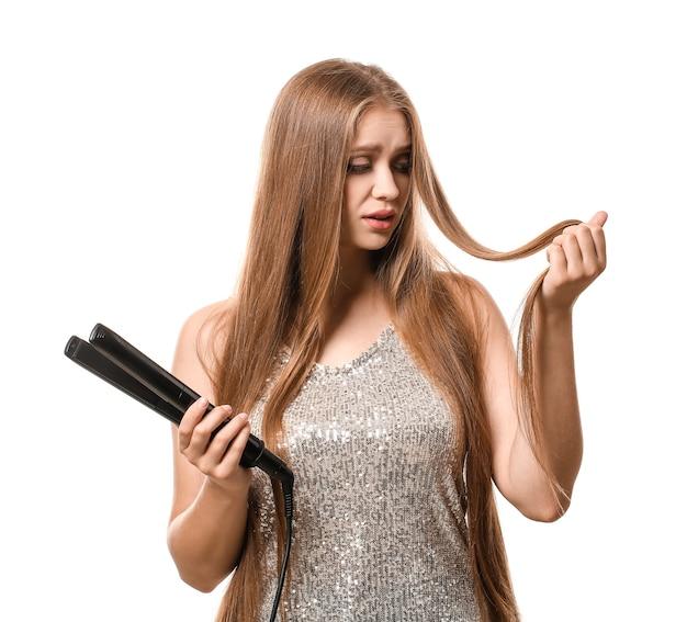 Bouleversé jeune femme avec un fer à repasser pour les cheveux sur fond blanc