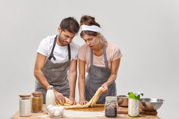 Bouleversé, jeune femme et homme pétrissent la pâte sans rouleau à pâtisserie, se sentent fatigués des longues heures de cuisine à la cuisine, n'ont aucune inspiration pour préparer des pâtisseries maison, sont sales avec de la farine, posent près de la table