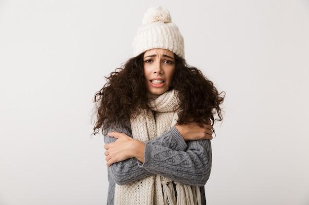Bouleversé jeune femme portant un foulard d'hiver debout isolé sur un mur blanc, grelottant
