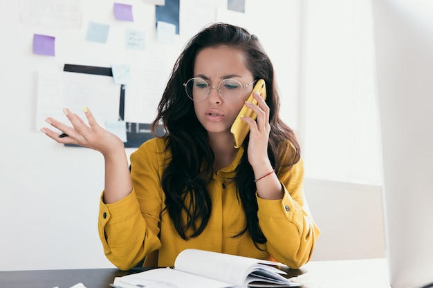 Bouleversé jeune femme s'asseoir au bureau de parler au téléphone déçu d'entendre de mauvaises nouvelles