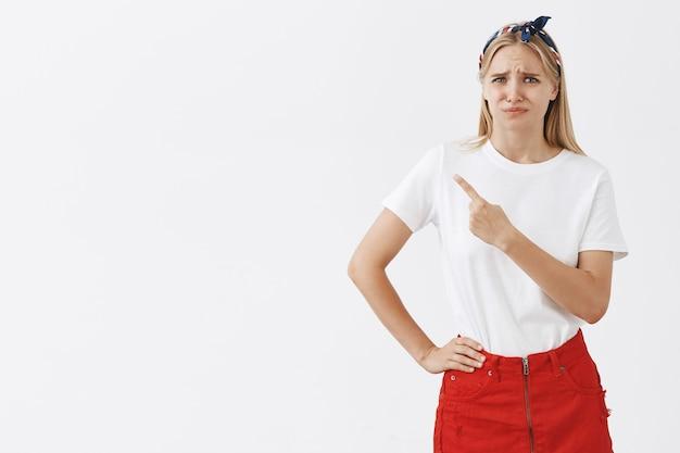 Bouleversé jeune fille blonde posant contre le mur blanc