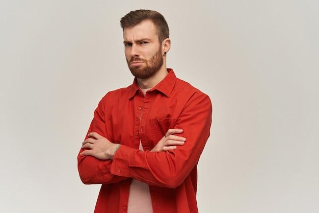Bouleversé malheureux jeune homme en chemise rouge avec barbe se sent triste et garde les bras croisés sur un mur blanc
